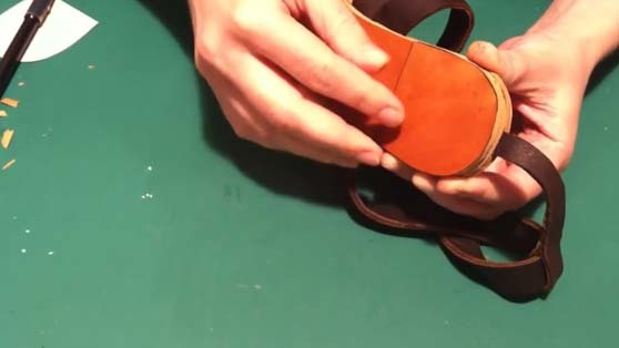 attaching the heel tap to the sandals sole in the process of handcrafted sandals making
